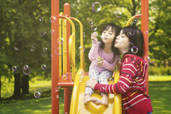 Mother and child blowing soap bubbles Stock Photography