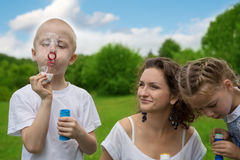 Mother and child blowing soap bubbles Stock Image