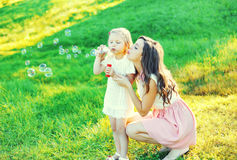 Mother with child blowing soap bubbles together on grass Stock Photography