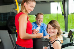 Mother and child boarding a bus. And buying a ticket Royalty Free Stock Photography
