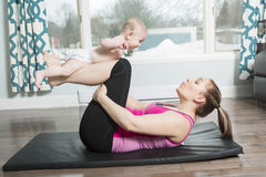 Mother with child boy doing fitness exercises. A Mother with child boy doing fitness exercises Royalty Free Stock Images