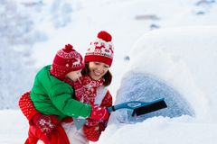 Mother and child brushing off car in winter. stock photo