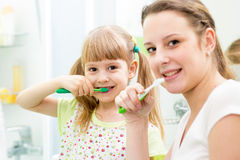 Mother and child brushing teeth in bathroom Royalty Free Stock Image
