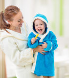Mother and child brushing teeth together in bathroom Stock Image