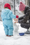Mother and child building a winter snowman Stock Photography