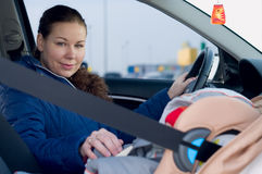 Mother and child in car safety seat. The child in a safety seat near to mother who sits on forward sitting of the car Stock Photography