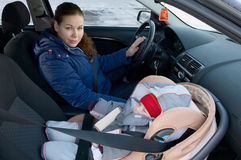 Mother and child in car safety seat. The child in a safety seat near to mother who sits on forward sitting of the car Stock Images