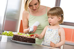 Mother and child with chocolate cake in kitchen Royalty Free Stock Images