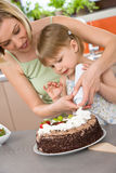 Mother and child with chocolate cake in kitchen Stock Images
