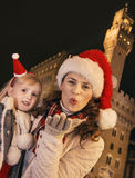 Mother and child in Christmas hats in Florence blowing air kiss Royalty Free Stock Images