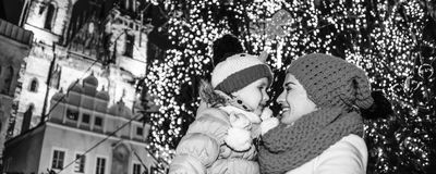 Mother and child in Christmas Prague looking at each other. Magic on streets of the old town at Christmas. smiling young mother and child tourists at Christmas Stock Images