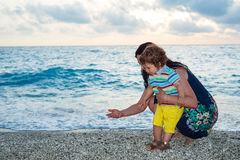 Mother and child collect pebbles on beach. Mother and her son collect little pebbles on the beach royalty free stock photography