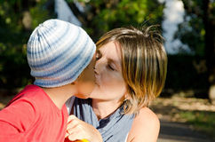 Mother with child color adopted. Adoptive mother kissing her baby Royalty Free Stock Photos