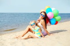 Mother and child with colorful balloons on beach near sea Royalty Free Stock Images