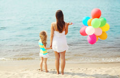 Mother and child with colorful balloons standing on beach near sea Royalty Free Stock Photo