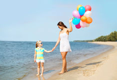 Mother and child with colorful balloons walking on beach Stock Photo