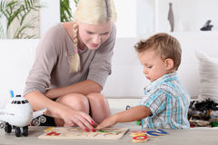 Mother and child completing jig-saw Royalty Free Stock Image