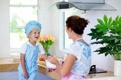 Mother and child cook. Mom and kid cook in kitchen royalty free stock images