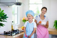 Mother and child cook. Mom and kid cook in kitchen stock images