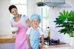 Mother and child cook. Mom and kid cook in kitchen stock photography