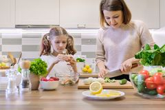 Mother and child cooking together at home in kitchen. Healthy eating, mother teaches daughter to cook, parent child communication royalty free stock photo