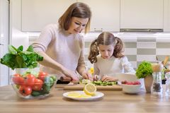 Mother and child cooking together at home in kitchen. Healthy eating, mother teaches daughter to cook, parent child communication stock image