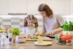 Mother and child cooking together at home in kitchen. Healthy eating, mother teaches daughter to cook, parent child communication stock photography