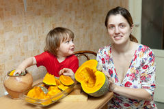 Mother with child cooks pumpkin Stock Image