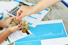 Mother and child counting money against business graphs, part of financial education lesson Royalty Free Stock Image