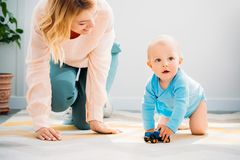 Mother and child crawling together on carpet. At home stock photos
