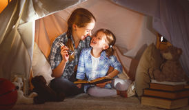 Mother and child daughter with a book and a flashlight before go. Reading and family games in children`s tent. mother and child daughter with  book and Royalty Free Stock Images