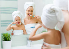 Mother and child daughter brush their teeth with  toothbrush Royalty Free Stock Images