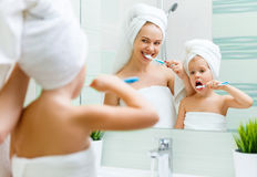 Mother and child daughter brush their teeth with  toothbrush Royalty Free Stock Photos