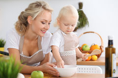 Mother and child daughter  cooking pasta or salad for the breakfast. Concept of happy family in the kitchen.  Stock Photography