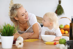 Mother and child daughter  cooking pasta or salad for the breakfast. Concept of happy family in the kitchen.  Royalty Free Stock Images