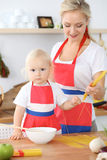 Mother and child daughter  cooking pasta or salad for the breakfast. Concept of happy family in the kitchen.  Stock Image