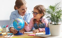 Mother and child daughter doing homework geography with globe royalty free stock photos