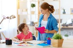 Mother and child daughter doing homework geography with globe. At home royalty free stock image