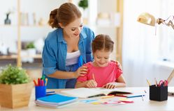 Mother and child daughter doing homework geography with globe. At home stock photos