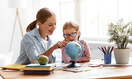 Mother and child daughter doing homework geography with globe. At home stock photo