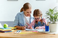 Mother and child daughter doing homework writing and reading at Royalty Free Stock Photography