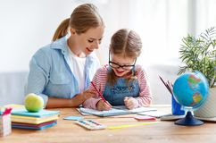 Mother and child daughter doing homework writing and reading at stock photo