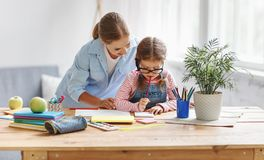 Mother and child daughter doing homework writing and reading at stock photography