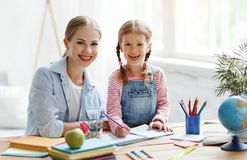 Mother and child daughter doing homework writing and reading at home stock photography