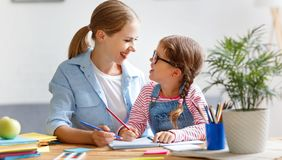 Mother and child daughter doing homework writing and reading at stock images