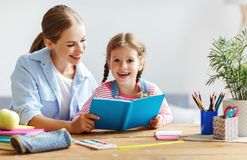 Mother and child daughter doing homework writing and reading at. Home stock photo