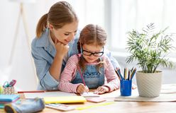 Mother and child daughter doing homework writing and reading at Stock Photos