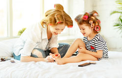 Mother and child daughter in hair curlers paint nails, make pedi Stock Photography