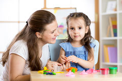 Mother and child daughter at home molded from clay and play together. Concept of preschool or home education. Royalty Free Stock Image