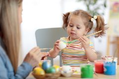 Mother and Daughter are painting eggs. Family are preparing for Easter. Mother and child daughter are painting eggs. Family are preparing for Easter holiday Royalty Free Stock Photos